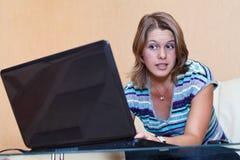 Mujer joven que juega en juegos en la computadora portátil Foto de archivo libre de regalías