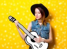 Mujer joven que juega en la guitarra de la imaginación Foto de archivo