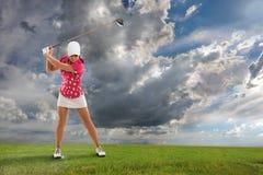 Mujer joven que juega a golf Imagen de archivo libre de regalías