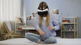 Mujer joven que juega a juegos usando los vidrios de las auriculares del vr en casa, experiencia asombrosa almacen de metraje de vídeo