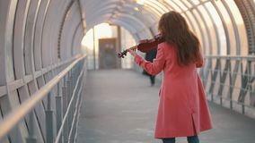 Mujer joven que juega la composici?n a solas del viol?n en la calle almacen de video