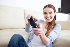 Mujer joven que juega a los videojuegos Imagen de archivo libre de regalías