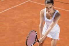 Mujer joven que juega a tenis Foto de archivo