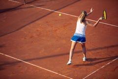 Mujer joven que juega a tenis en la arcilla forehand imagen de archivo