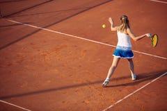 Mujer joven que juega a tenis en la arcilla forehand imágenes de archivo libres de regalías
