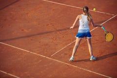 Mujer joven que juega a tenis en la arcilla forehand foto de archivo