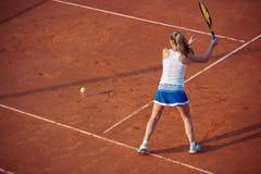 Mujer joven que juega a tenis en la arcilla forehand imagenes de archivo