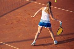 Mujer joven que juega a tenis en la arcilla forehand fotografía de archivo libre de regalías
