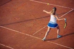 Mujer joven que juega a tenis en la arcilla forehand fotografía de archivo