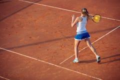 Mujer joven que juega a tenis en la arcilla forehand foto de archivo libre de regalías