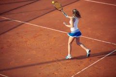 Mujer joven que juega a tenis en la arcilla forehand fotos de archivo