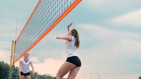 Mujer joven que juega a voleibol en la playa en un equipo que realiza un ataque que golpea la bola Muchacha en golpes de la cámar almacen de video