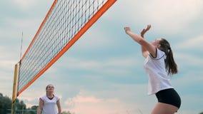 Mujer joven que juega a voleibol en la playa en un equipo que realiza un ataque que golpea la bola Muchacha en golpes de la cámar metrajes