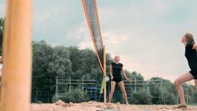 Mujer joven que juega a voleibol en la playa en un equipo que realiza un ataque que golpea la bola Muchacha en golpes de la cámar almacen de metraje de vídeo
