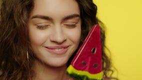 Mujer joven que lame el caramelo en estudio Cara del modelo de moda que sonr?e in camera metrajes