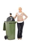 Mujer joven que lanza hacia fuera la basura Imágenes de archivo libres de regalías
