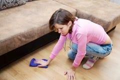 Mujer joven que lava el piso de madera con el floorcloth azul fotos de archivo