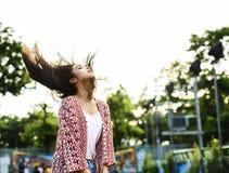 Mujer joven que le arroja el pelo en un parque de atracciones Foto de archivo