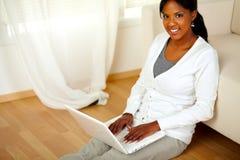 Mujer joven que le mira que hojea el Internet Imagen de archivo libre de regalías