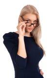 Mujer joven que le mira sobre los vidrios Fotos de archivo