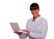 Mujer joven que le mira usando el ordenador portátil Fotos de archivo