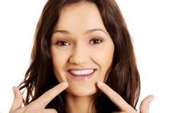 Mujer joven que le muestra los dientes perfectos Imagen de archivo libre de regalías