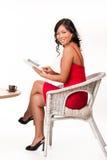 Mujer joven que lee el libro electrónico Imagen de archivo