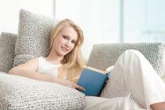 Mujer joven que lee el libro en el sofá Fotografía de archivo