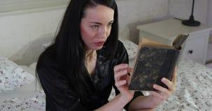 Mujer joven que lee el libro viejo en la cama que lleva la bata negra - emociones de la cara almacen de video