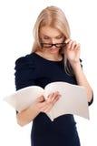 Mujer joven que lee la revista para mujer Imagen de archivo