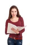 Mujer joven que lee la revista para mujer Imagenes de archivo
