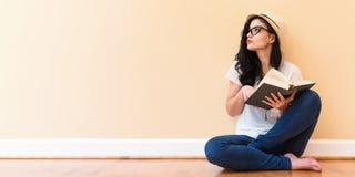 Mujer joven que lee un libro Foto de archivo libre de regalías