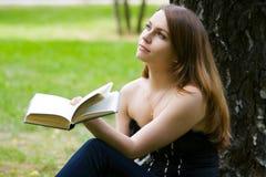 Mujer joven que lee un libro. Imagen de archivo libre de regalías