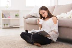 Mujer joven que lee un libro Imágenes de archivo libres de regalías