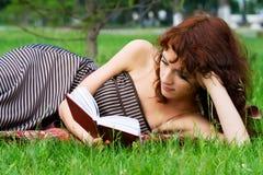 Mujer joven que lee un libro. Imagen de archivo