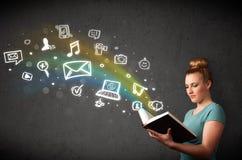 Mujer joven que lee un libro con los iconos de las multimedias que salen de t Foto de archivo libre de regalías
