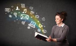 Mujer joven que lee un libro con los iconos de las multimedias que salen de t Fotografía de archivo libre de regalías