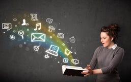 Mujer joven que lee un libro con los iconos de las multimedias que salen de t Imagen de archivo libre de regalías