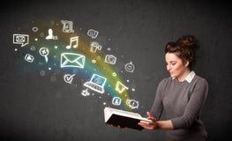 Mujer joven que lee un libro con los iconos de las multimedias que salen de t Imagenes de archivo