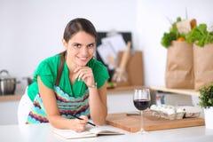 Mujer joven que lee un libro de la receta en la cocina fotografía de archivo libre de regalías