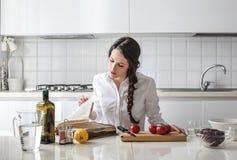 Mujer joven que lee un libro del cocinero Imagenes de archivo