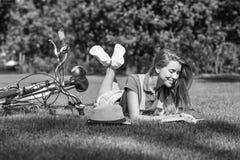 Mujer joven que lee un libro después de completar un ciclo en el parque local Fotos de archivo libres de regalías