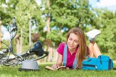 Mujer joven que lee un libro después de completar un ciclo en el parque local Foto de archivo libre de regalías