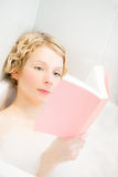 Mujer joven que relaja y que lee un libro en el baño Imagen de archivo libre de regalías