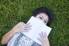 Mujer joven que lee un libro en el campo Imagen de archivo