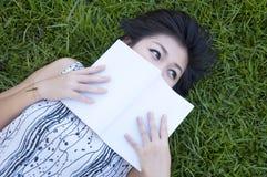 Mujer joven que lee un libro en el campo Imagen de archivo libre de regalías