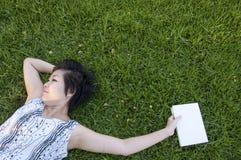 Mujer joven que lee un libro en el campo Foto de archivo libre de regalías