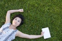 Mujer joven que lee un libro en el campo Fotos de archivo