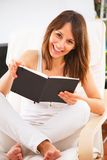 Mujer joven que lee un libro en el cuarto Imagen de archivo