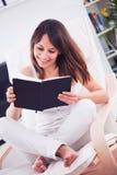 Mujer joven que lee un libro en el cuarto Foto de archivo